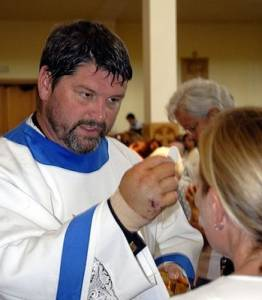 Father Rick Wendell giving Communion